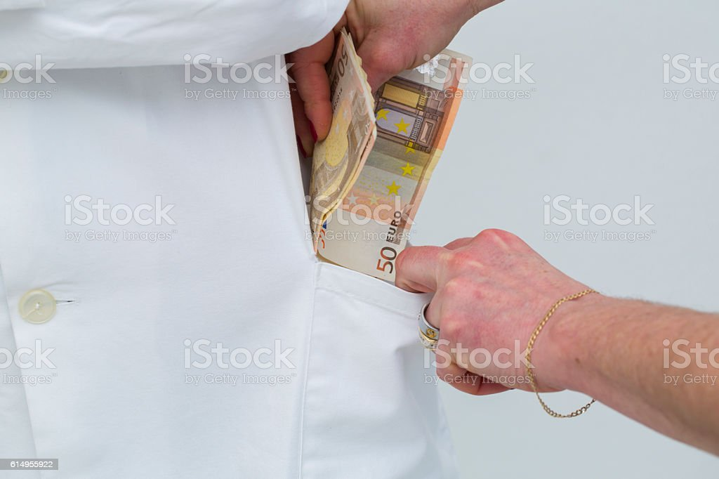 Corrupted doctor taking bribes money,white collar crime stock photo