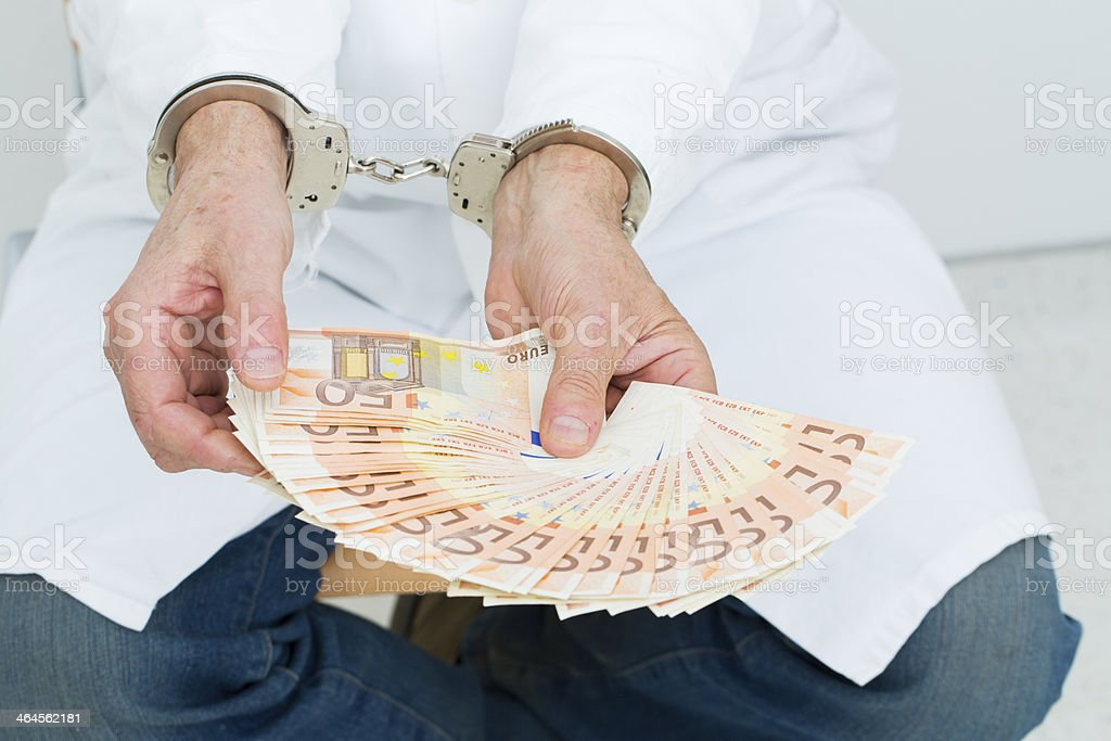 Corrupted doctor with money and handcuffs,arrested stock photo