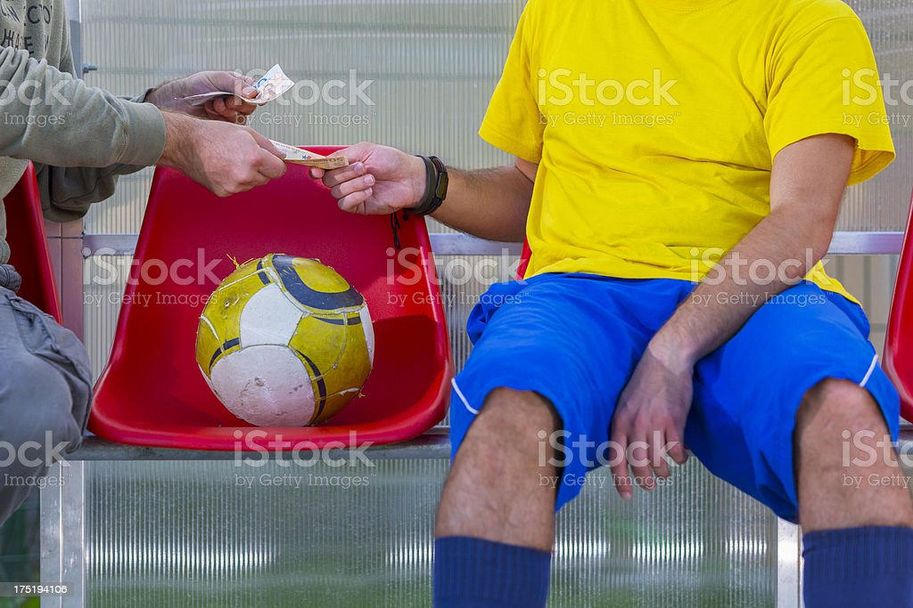 Corrupted professional soccer player taking money royalty-free stock photo