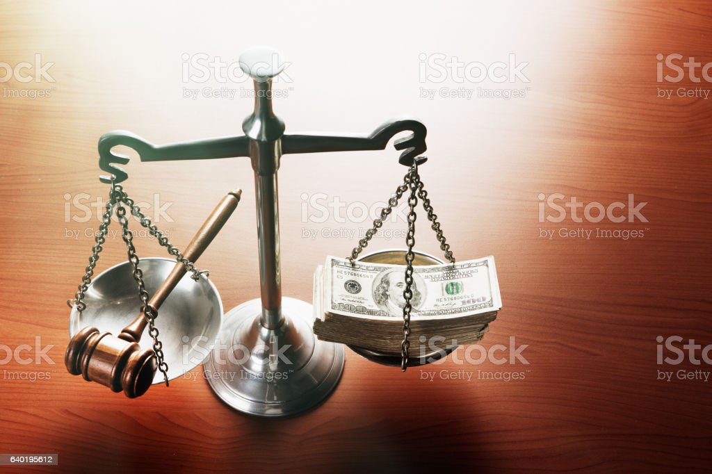 Corruption in court? Scales of Justice with stacks of dollars stock photo
