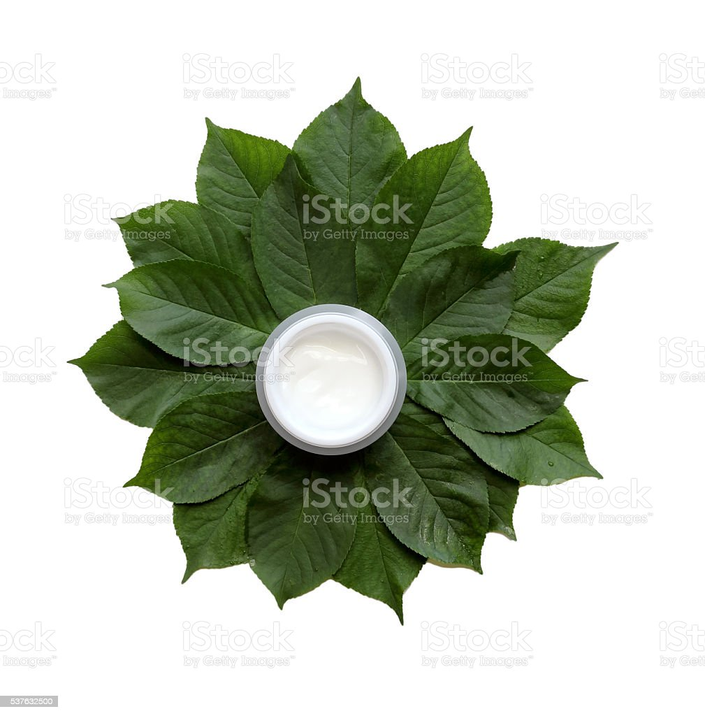 cosmetic cream on a stack of green leaves, isolated stock photo