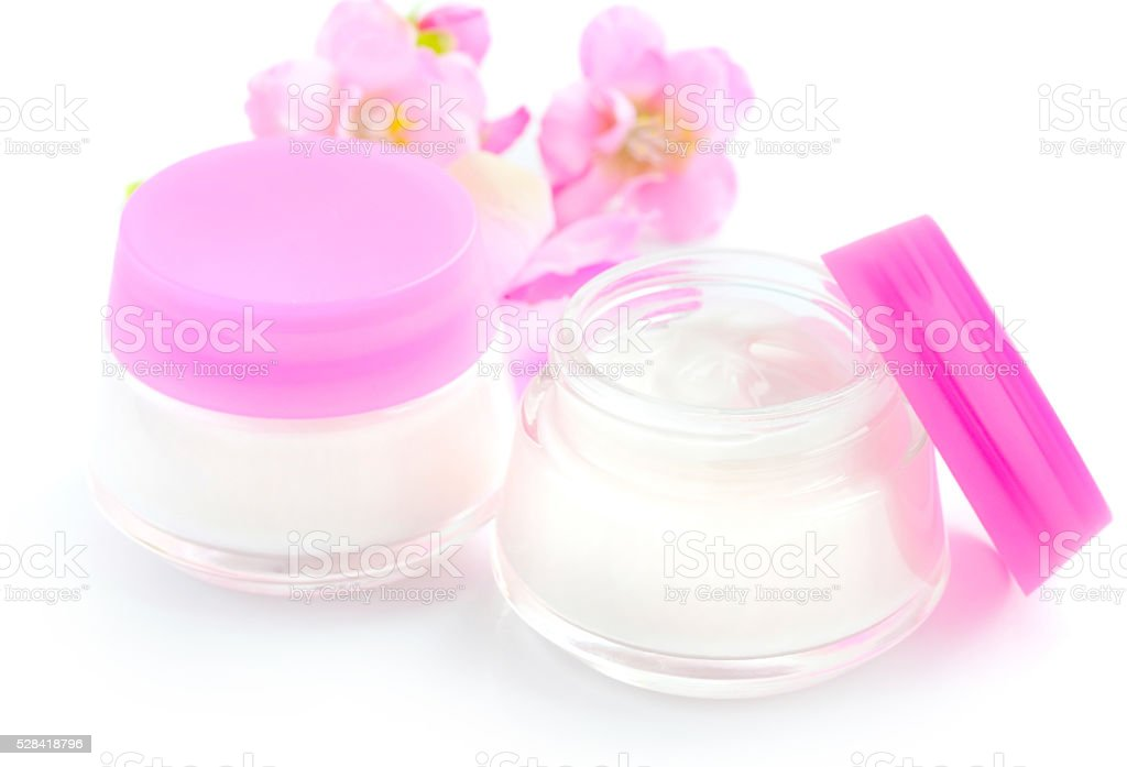 Cosmetic creams and pink flowers isolated on white background stock photo