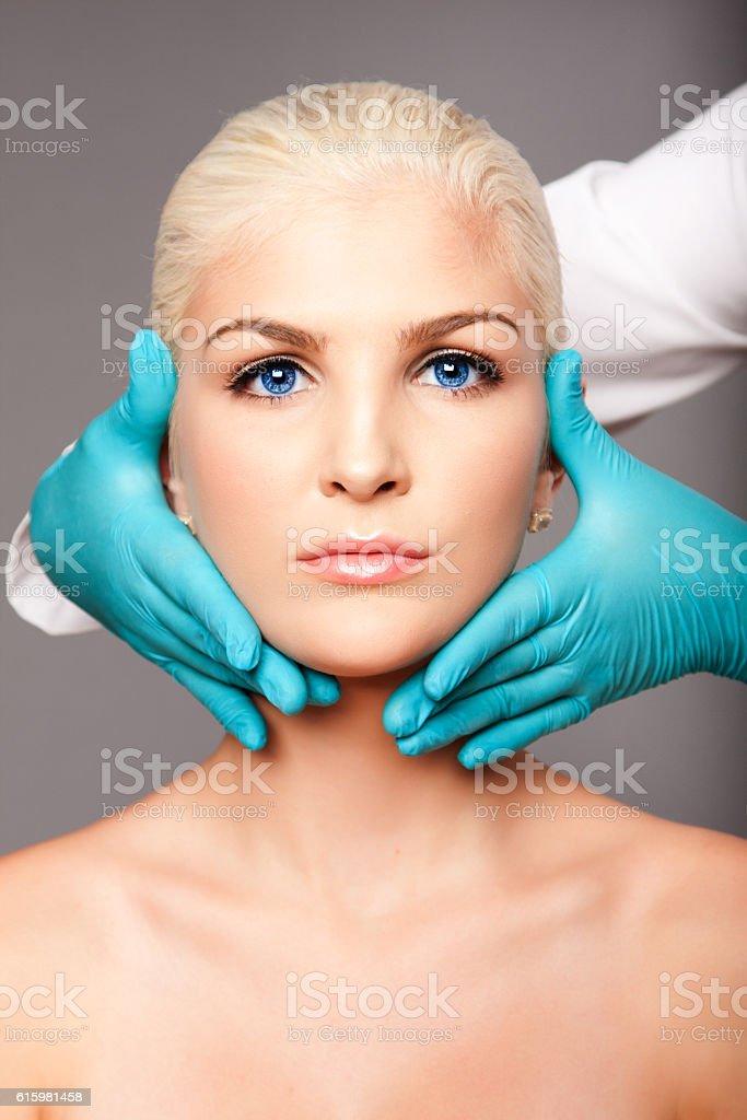 Cosmetic plastic surgeon touching aesthetics face stock photo