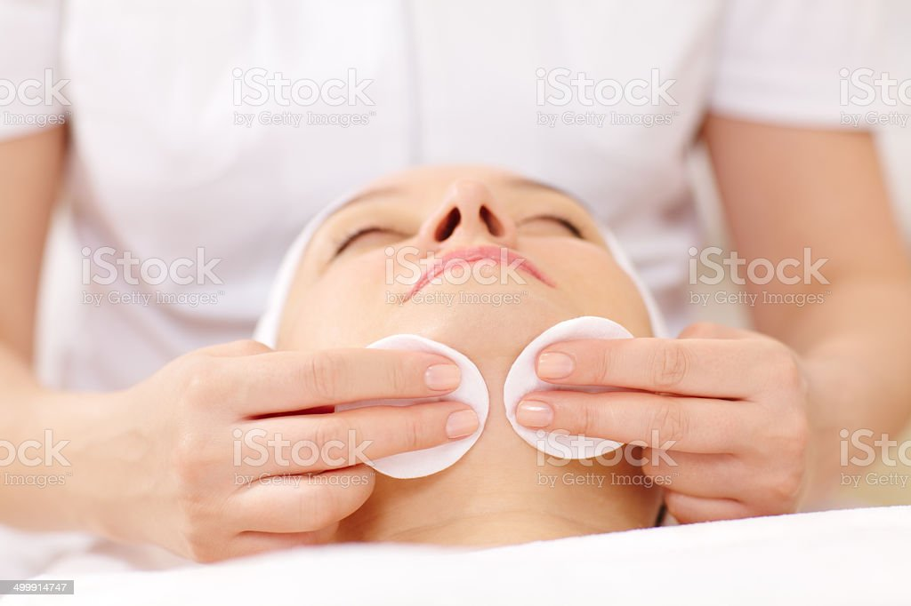 Cosmetician cleaning face using cotton pads stock photo