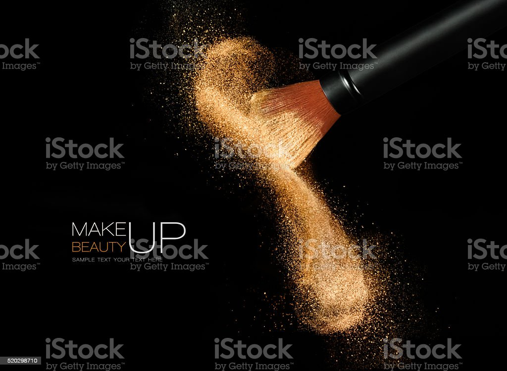 Cosmetics brush with glowing face powder. Dust explosion stock photo