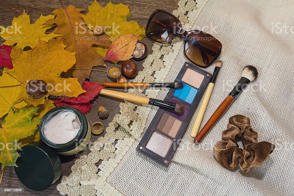 Cosmetics, sunglasses, autumn leaves on a wooden table stock photo