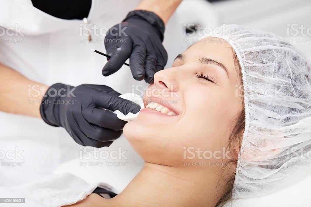 Cosmetologist applying permanent make up on lips stock photo