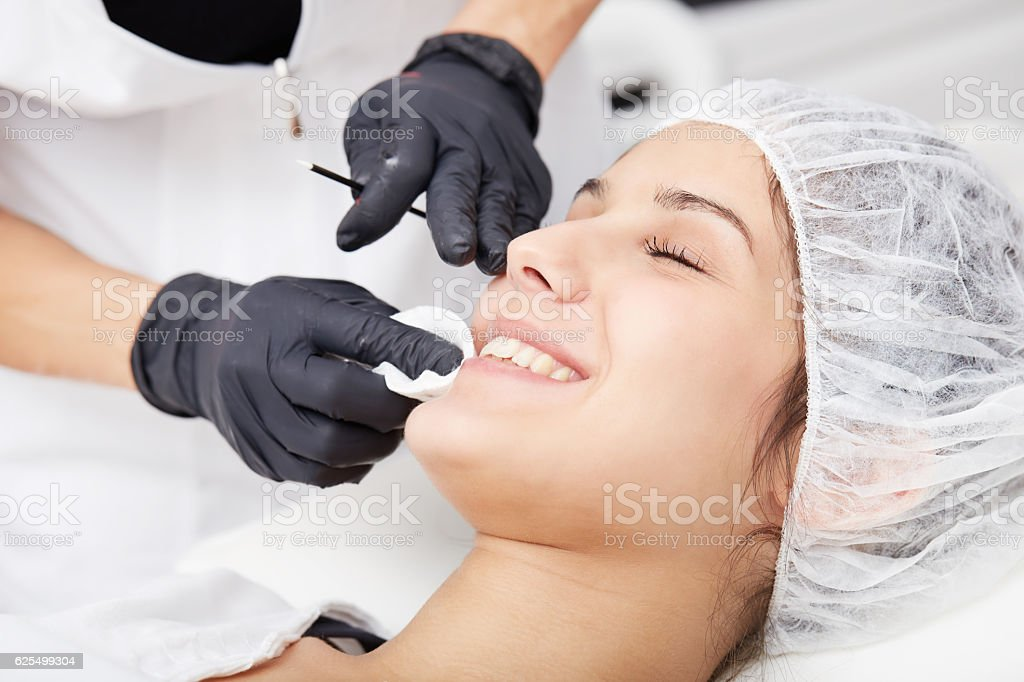 Cosmetologist applying permanent make up on lips stock photo