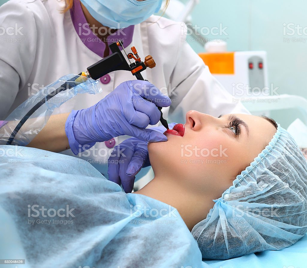 Cosmetologist making permanent makeup on woman's face royalty-free stock photo