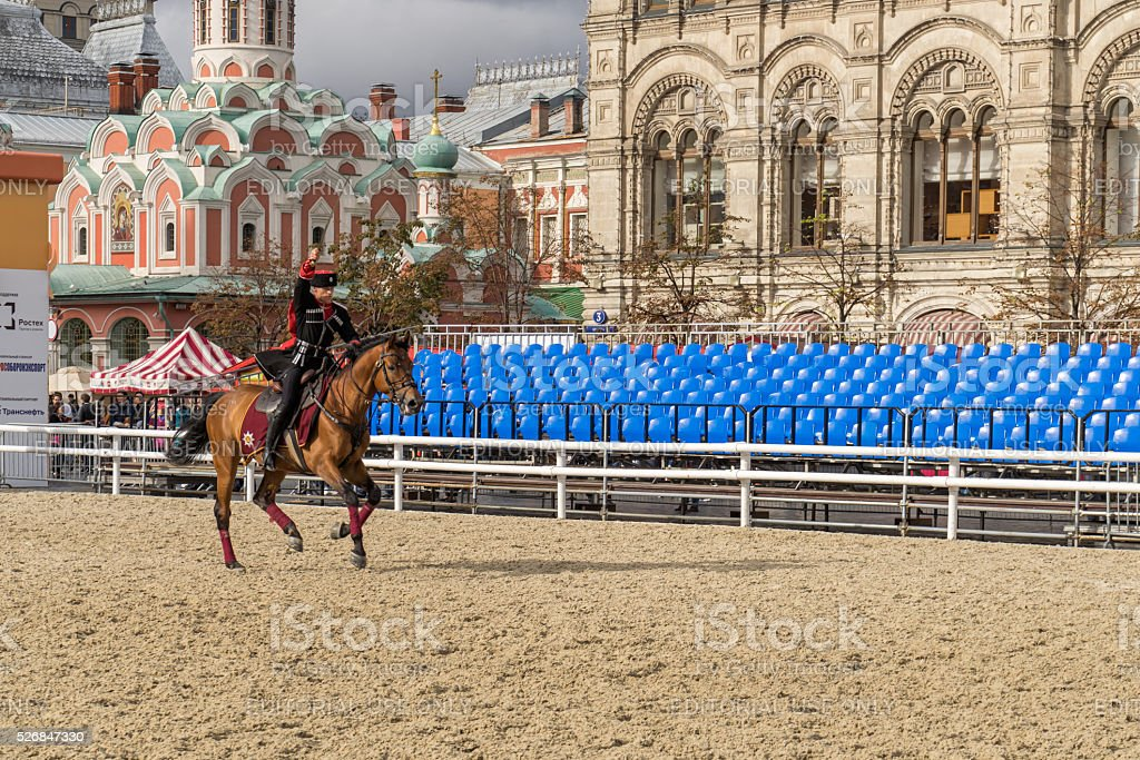 Cossack in full-dress uniform demonstrates skill of trick riding stock photo