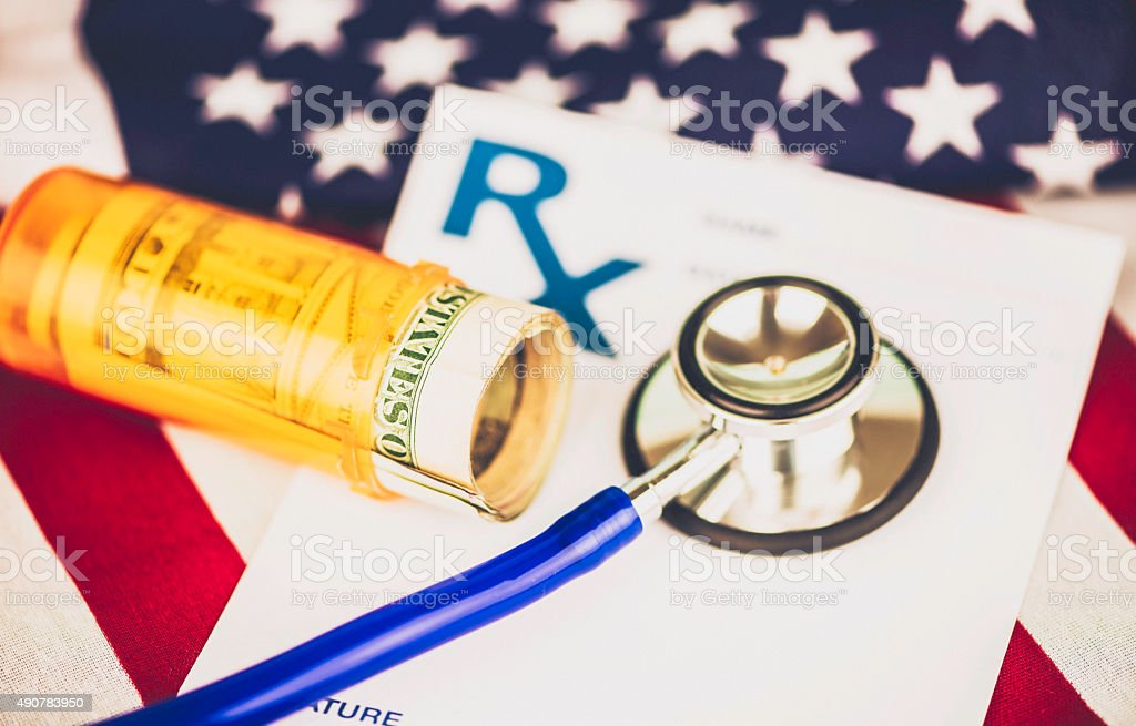 Cost of American healthcare. Dollars in pill bottle on flag. stock photo