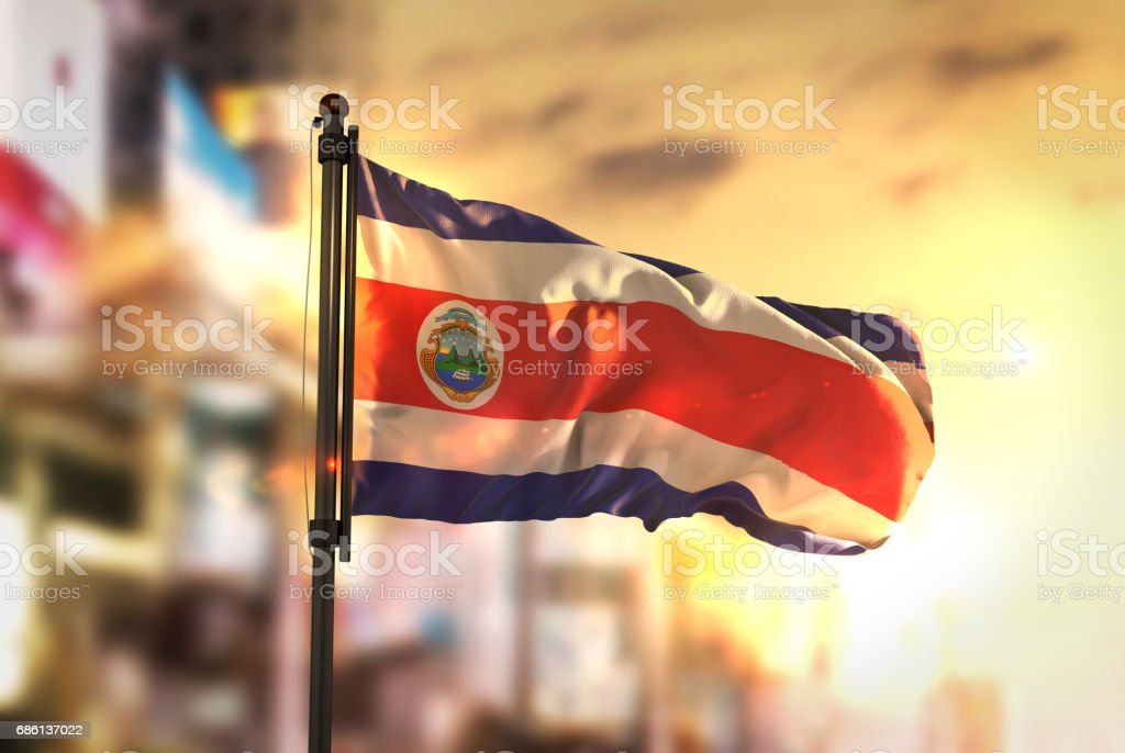 Costa Rica Flag Against City Blurred Background At Sunrise Backlight stock photo
