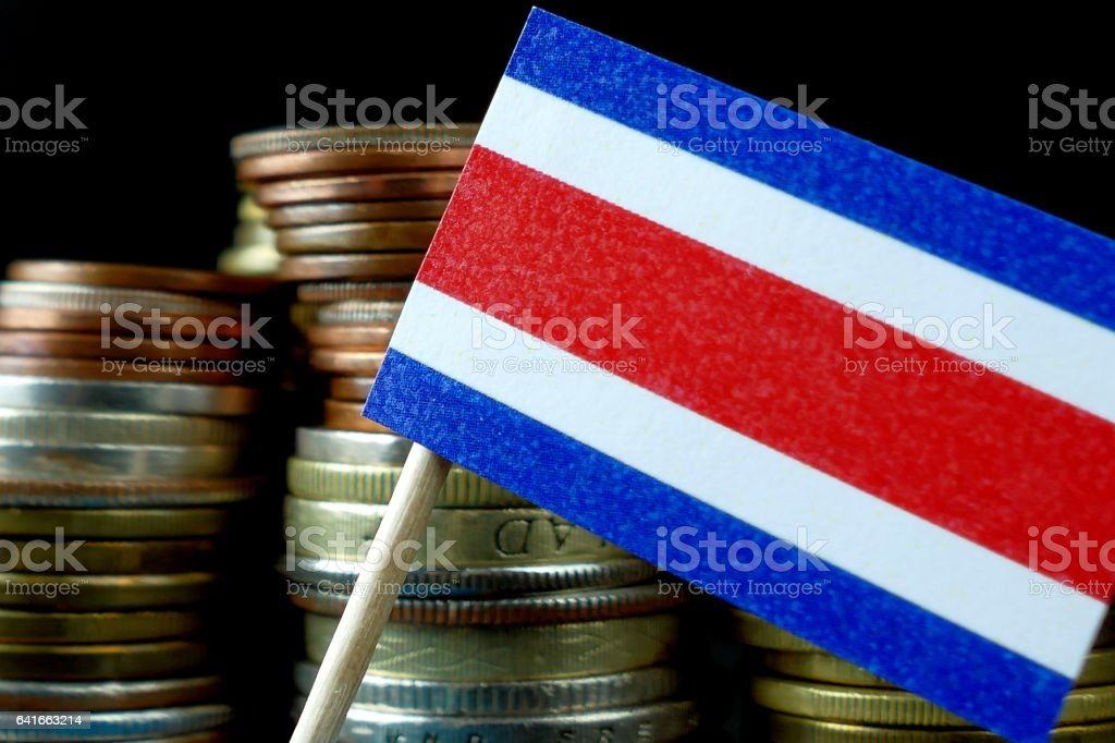 Costa Rica flag waving with stack of money coins macro stock photo