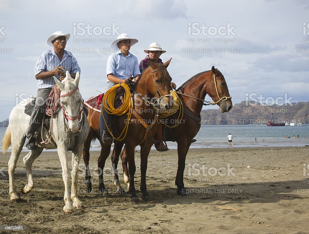 Costa Rican cowboys on the beach in Playas del Coco stock photo