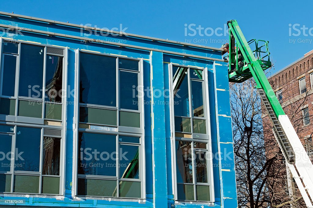 Costruction worker on cherry picker at office building stock photo