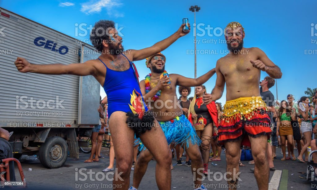 Costumed man in a leotard with hair and fire between his legs with two his friends in mini skirts in Flamengo Park, Carnaval 2017 stock photo