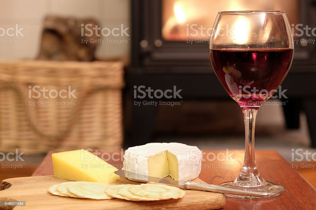 Cosy evening by fire with wine and cheese stock photo