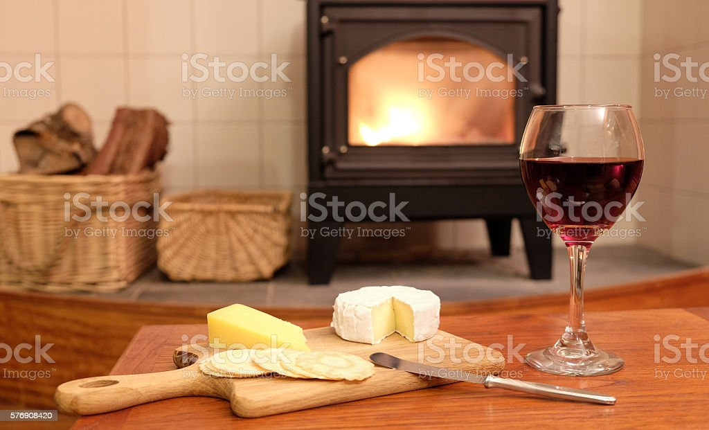 Cosy evening by woodburner fire with wine and cheese stock photo