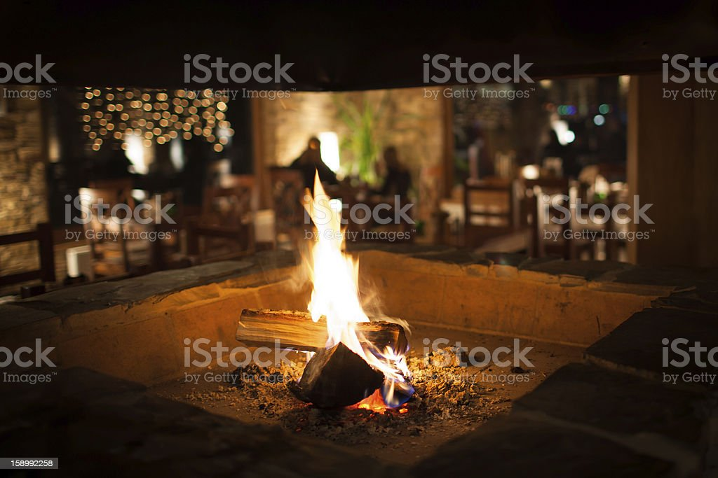 Cosy fireplace in a mountain chalet's warm, wooden interior stock photo