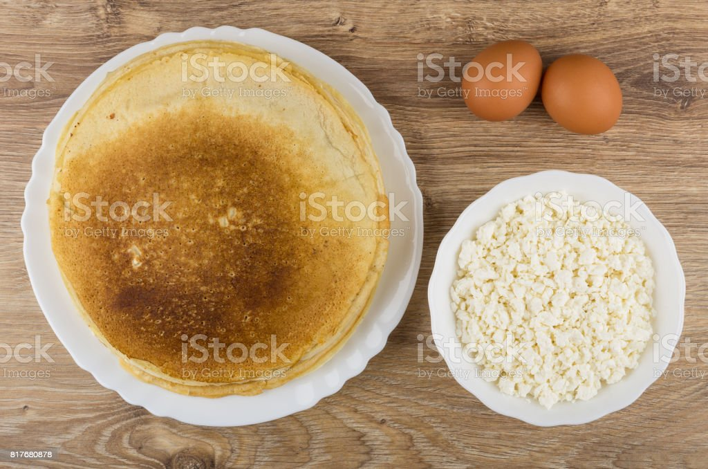 Cottage cheese, eggs and pancakes in white bowl on table stock photo