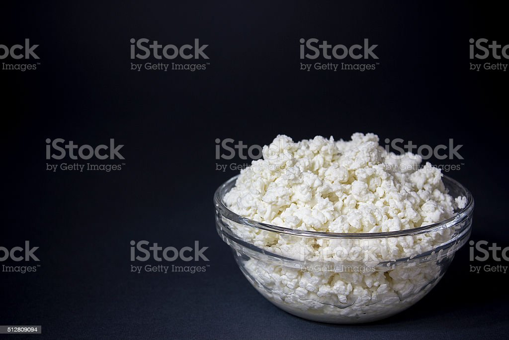 Cottage cheese in a glass bowl. Background. Space for text stock photo