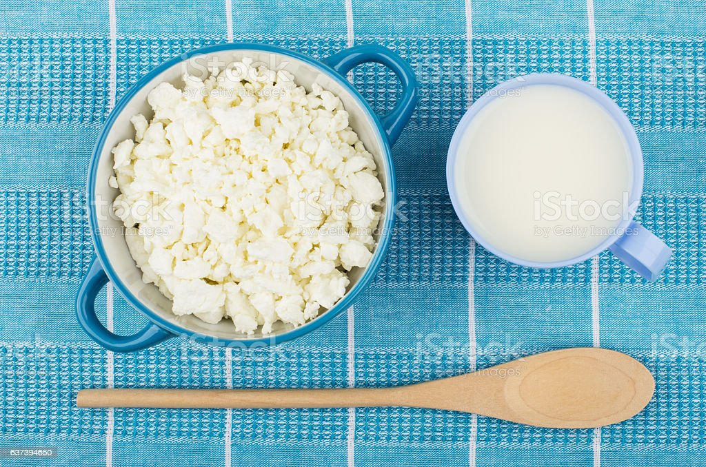 Cottage cheese in blue bowl, cup of milk and spoon stock photo