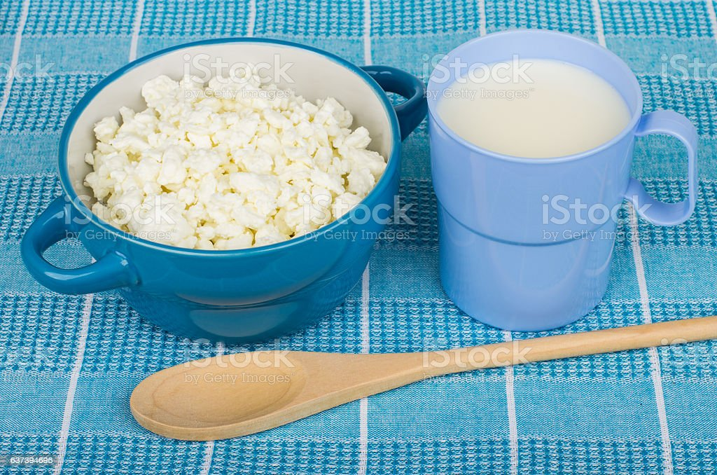 Cottage cheese in bowl, cup of milk and wooden spoon stock photo