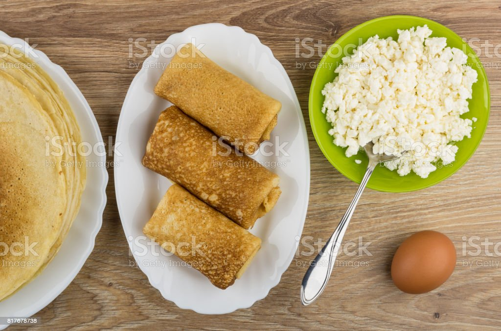 Cottage cheese in bowl, prepared pancakes in dish and egg stock photo