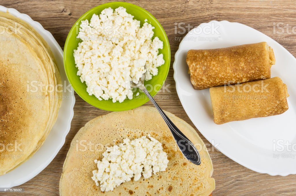 Cottage cheese in bowl, stuffing on pancakes and prepared pancakes stock photo