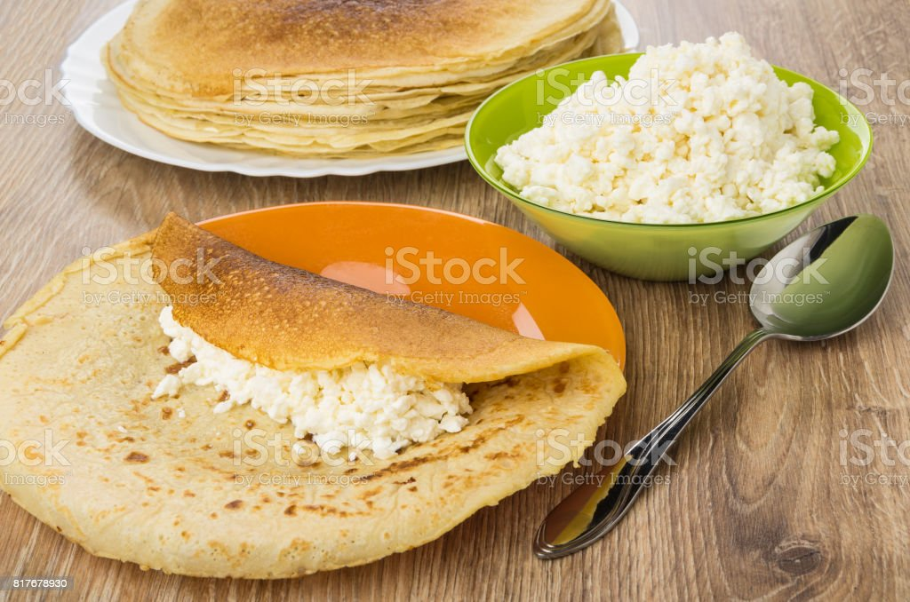 Cottage cheese in green bowl, stuffing on pancakes stock photo