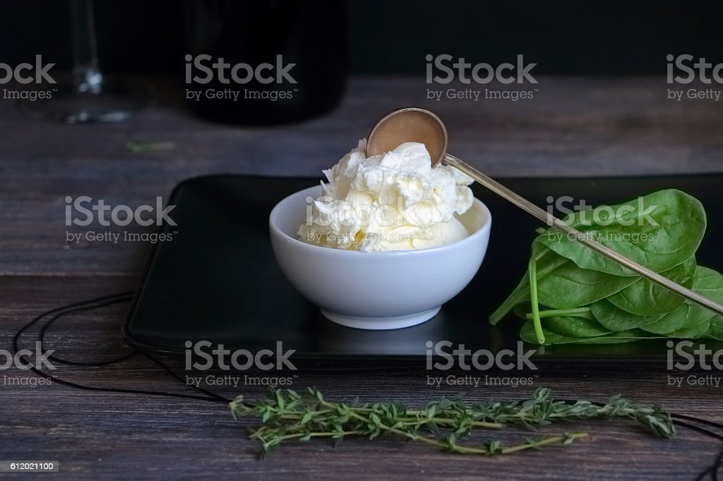 Cottage cheese, mascarpone n porcelain bowl  against black background stock photo