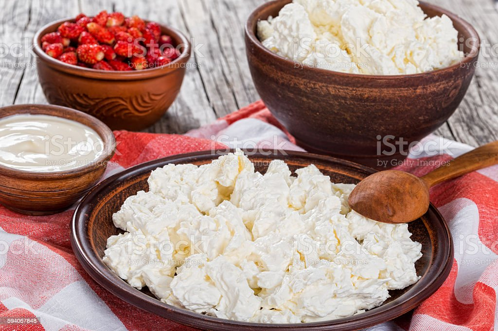cottage cheese on clay plate, sour creamand strawberry in bowls stock photo