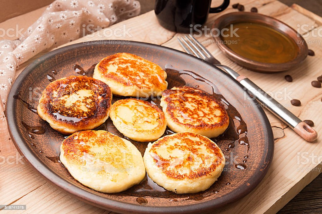 Cottage cheese pancakes with honey on brown ceramic plate stock photo