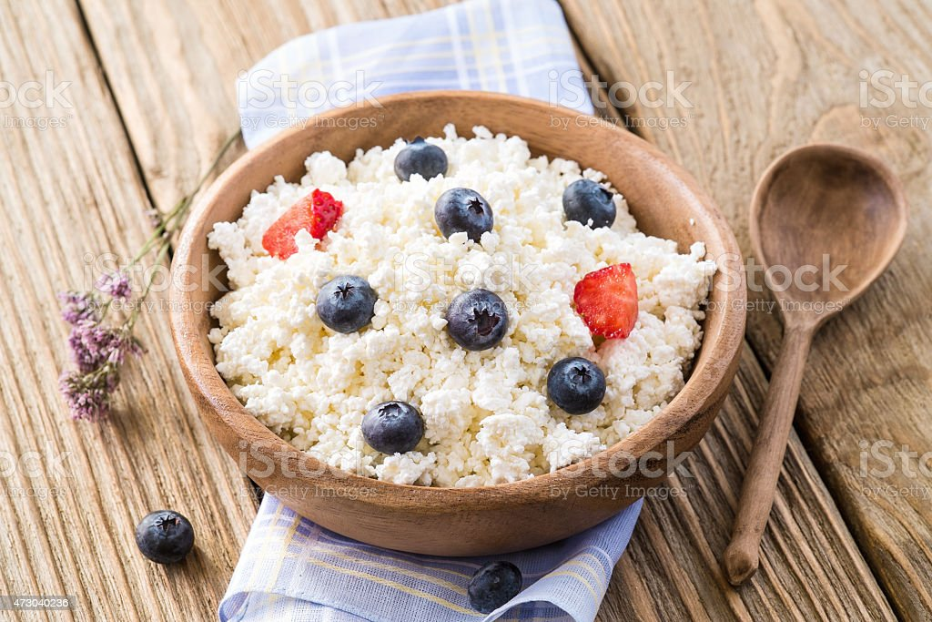 Cottage cheese with ripe blueberries in a wooden plate stock photo