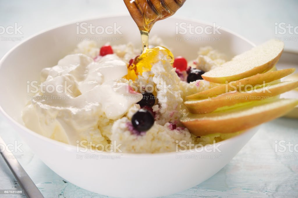 Cottage cheese with sour cream, fruits and honey stock photo