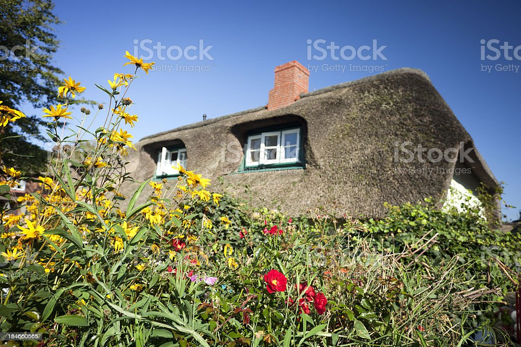 Cottage with thatched straw roof stock photo