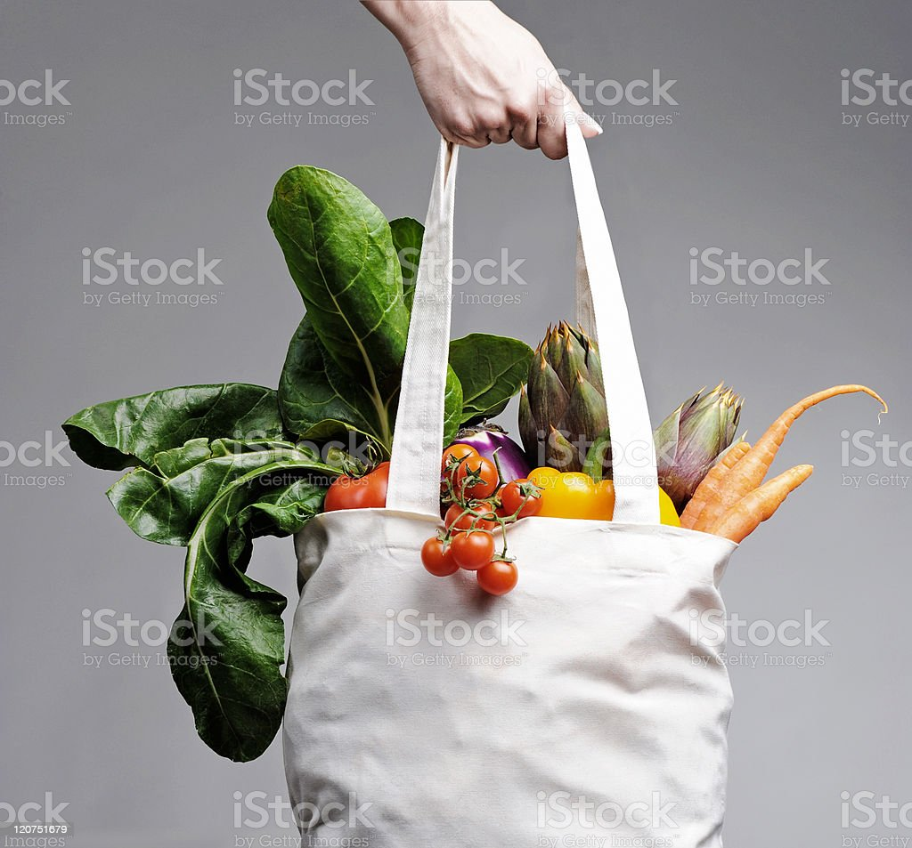 Cotton shopping bag overflowing with vegetables stock photo