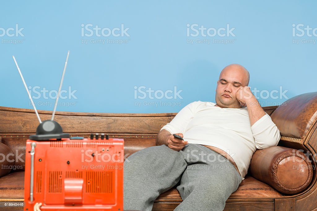Couch Potato Sitting On Sofa And Watching Television stock photo