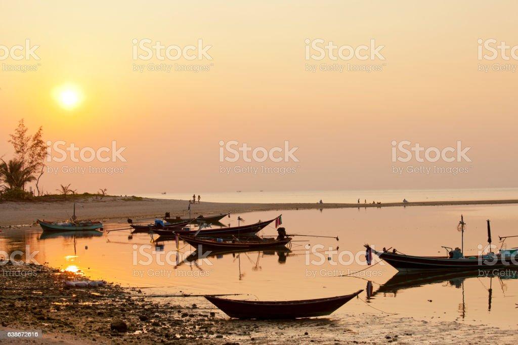coucher de soleil sur des barques dans l'eau stock photo