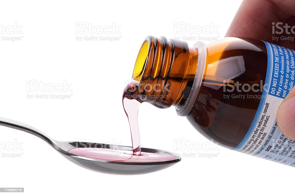 Cough syrup being poured on a spoon stock photo