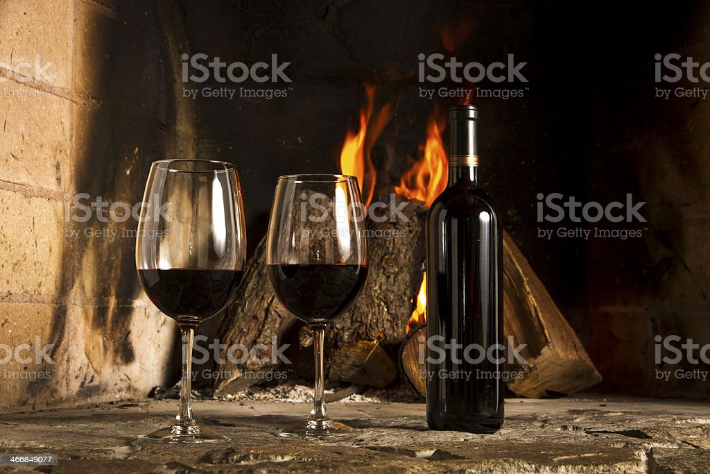 Coulpe of red wine cups and bottle, fireplace background. royalty-free stock photo