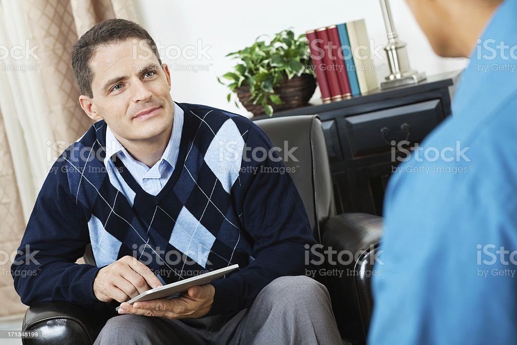 Counselor taking notes with digital tablet during meeting royalty-free stock photo