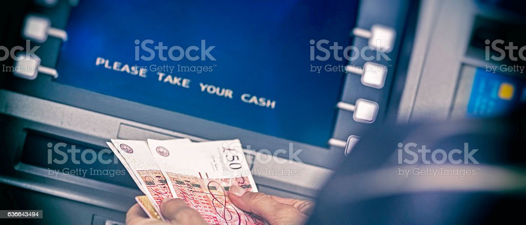 Counting British pounds from ATM machine stock photo