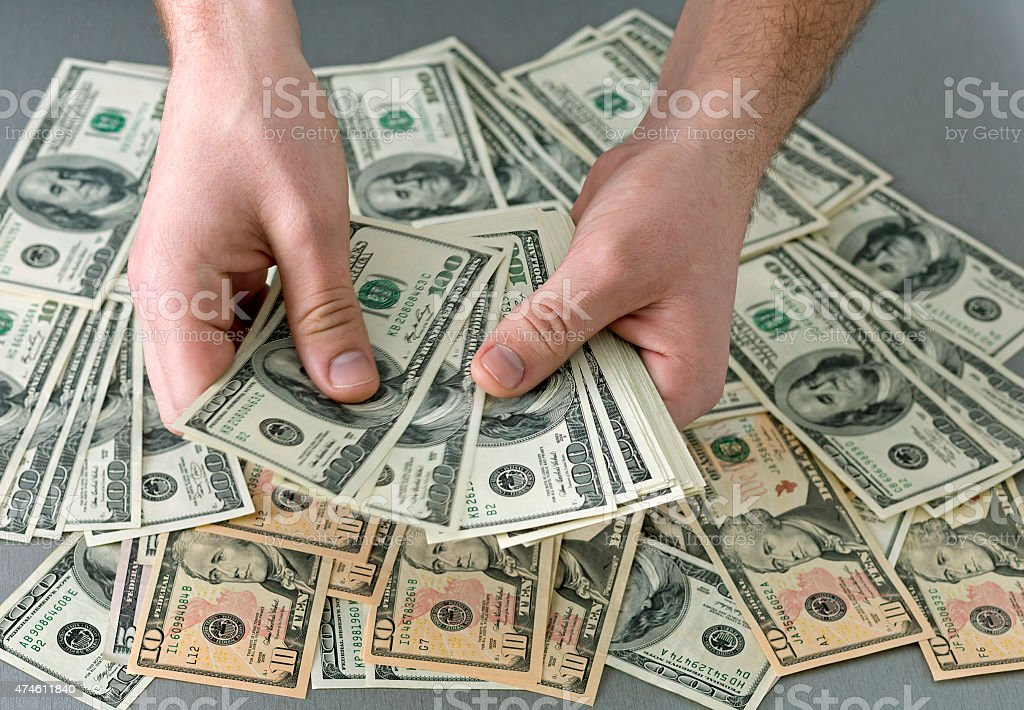 Counting large stack of cash notes stock photo
