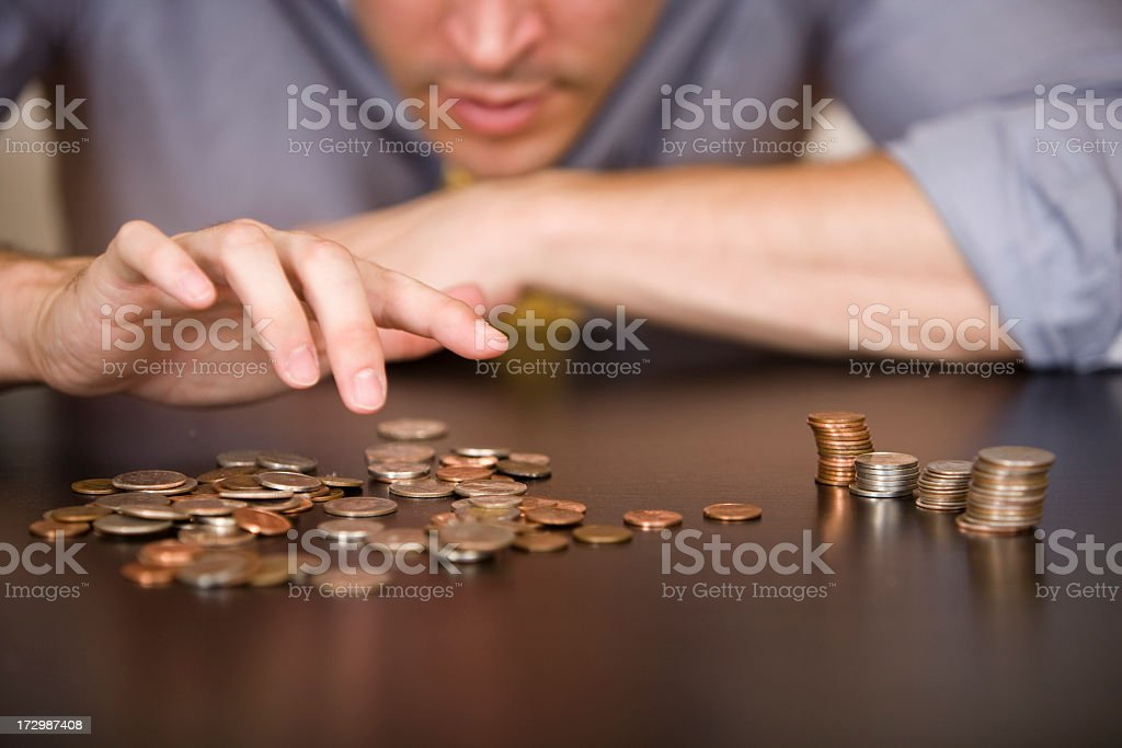 Counting or sorting coins, with 4 piles of different types stock photo
