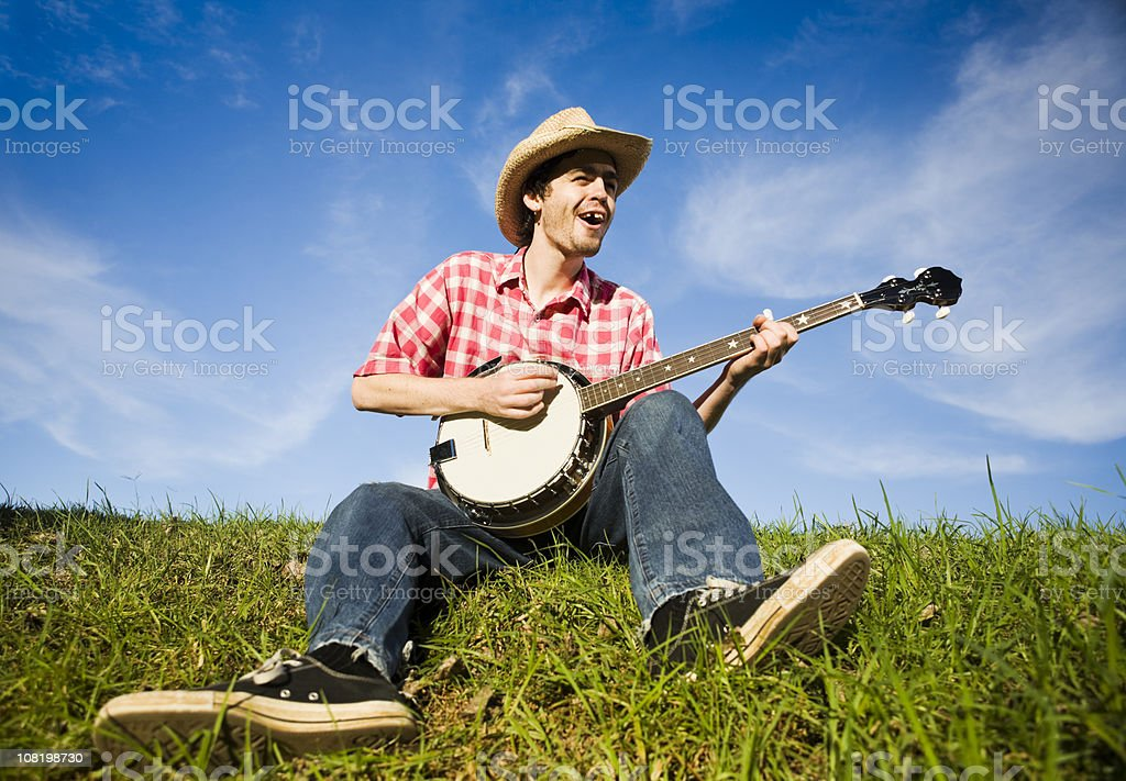 Country boy plays the banjo in a rural summer meadow stock photo