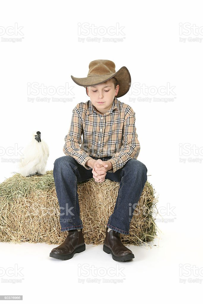 Country boy sitting on lucerne bale stock photo