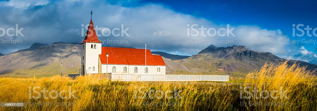 Country church with red roof in grassy pasture below mountains stock photo