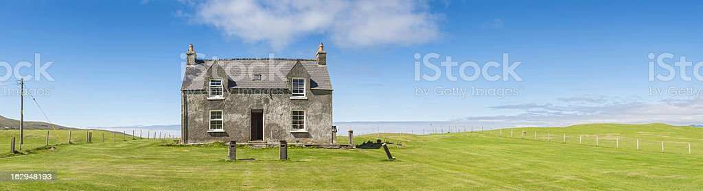 Country cottage in vibrant green fields under blue summer skies royalty-free stock photo