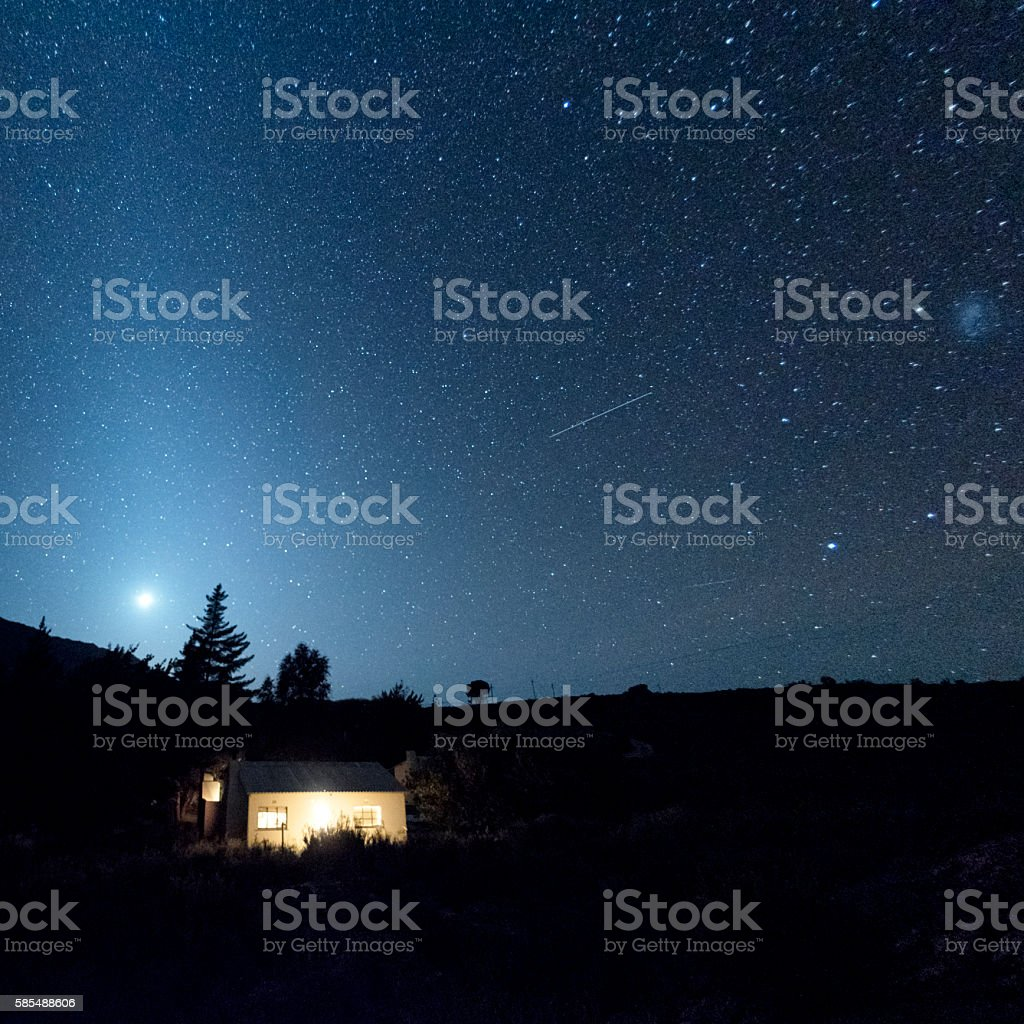 Country cottage with sky at night stock photo